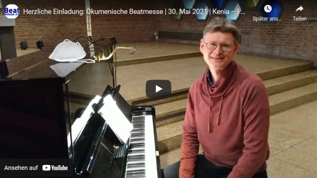 Pfarrer Ivo Masanek sitzt am Klavier. Der Link führt zum Einladungsvideo auf YouTube.